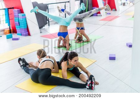 Young women practicing yoga in fitness hall doing headstand with legs spread wide apart and partner side seated wide angle pose