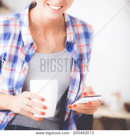 Smiling woman holding her cellphone in the kitchen.