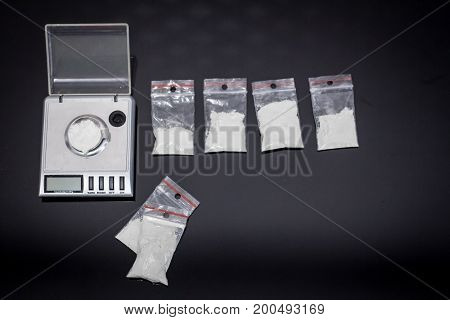 scales with cocaine and money on black table
