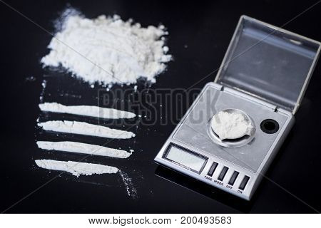 Cocaine in packages, dollars, knife on black background
