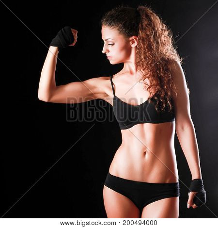 Portrait of young beautiful fitness woman, isolated on black background.