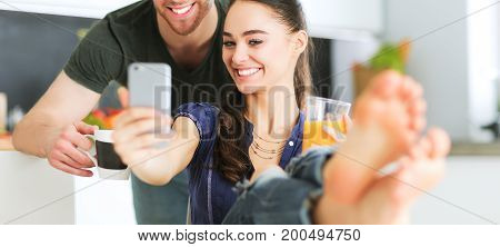 Happy couple using smartphone sitting in kitchen.