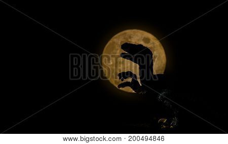 dinosaur with full moon silhouette on dark night