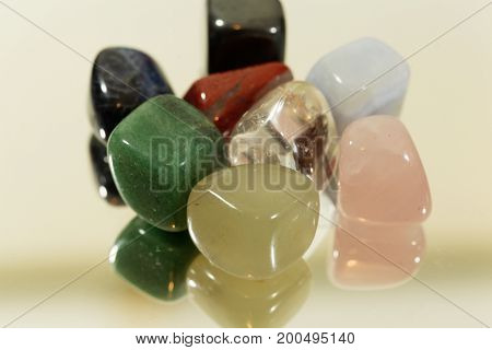 Several pieces of tumbled gemstones on a mirror.