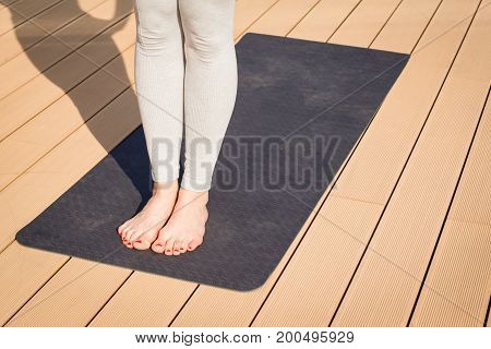 close up picture of yoga mat on wooden floor and legs of woman in asana