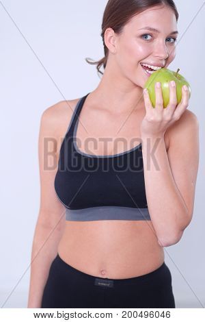 Happy young woman eating apples, isolated on white background