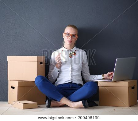 Woman sitting on the floor near a boxes with laptop . Businesswoman.