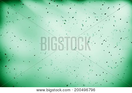 Dust particles on green paper texture background