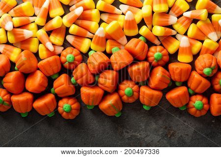 Candy corn and pumpkin Halloween background overhead shot with copy space