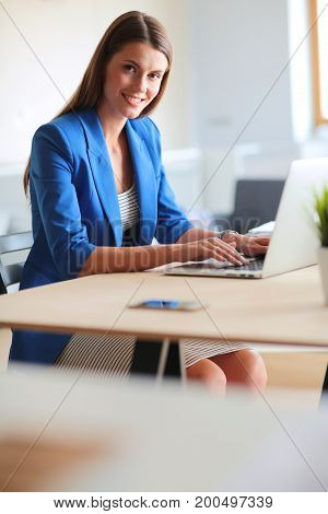 Woman sitting on the desk with laptop.