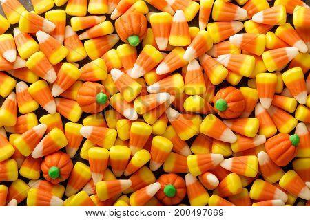 Candy corn and pumpkin Halloween background overhead shot