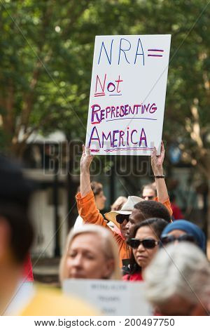 ATLANTA, GA - APRIL 2017:  A woman holds up a sign that says