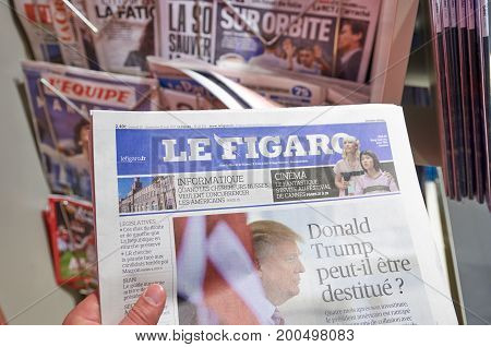 LONDON ENGLAND - MAY 14 2017 : A hand holding Le Figaro newspaper over newsstand background in Paris. Le Figaro is a French daily morning newspaper founded in 1826 and published in Paris.