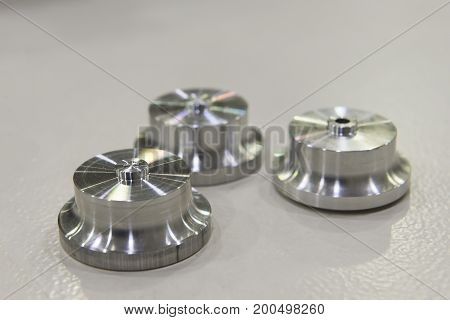 The parts from turning or lathe process on the white metal floor.Machine part