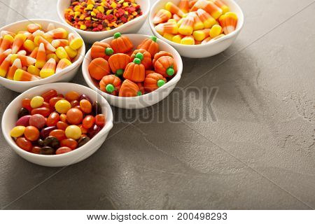 Halloween candy and sprinkles in white bowls with copy space