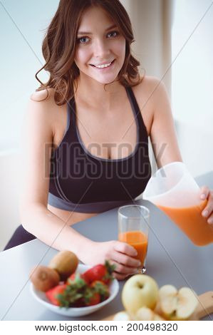 Girl sitting in the kitchen with fruit and glass with juice.