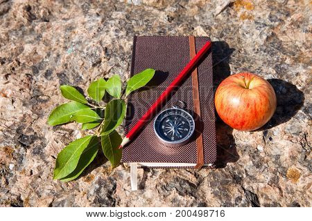 Notebook, Compass, Apple On Stone Background