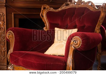 An Ancient Wooden Chair Upholstered In A Red Cloth
