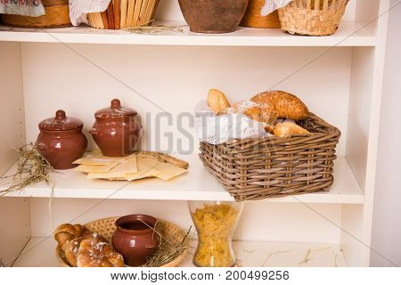 Rack With Buns In A Wicker Box And Clay Pots