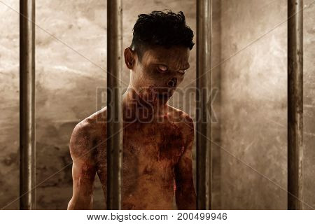 Angry scary zombie in trapped dirty  prison