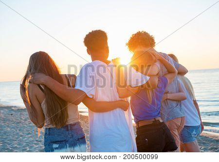 Group of happy friends having fun at ocean beach at dawn
