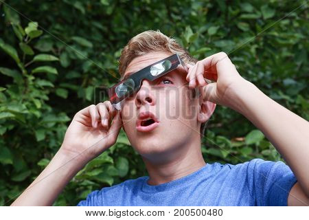 Boy peeking at the sun during an eclipse