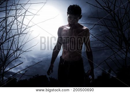 Scary zombie on spooky forest at night