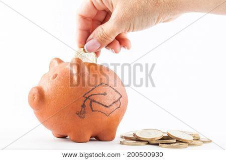 Close up of a woman saving money into a traditional clay piggy bank to study