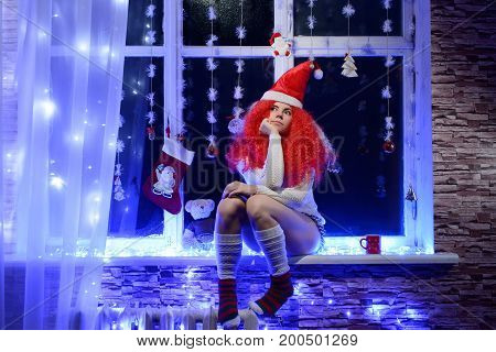 Young woman in Christmas hat sitting on window