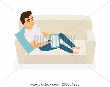 Man seating on couch and use tablet. Guy communicates, orders food, gets education online or works at home on sofa. Freelancer at home. Leisure and relax.