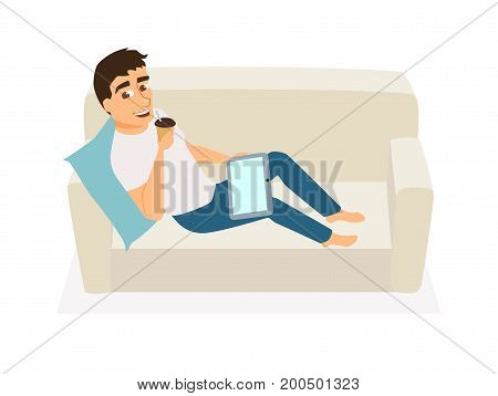 Man seating on couch, use tablet and drink coffee. Guy communicates, orders food, gets education online or works at home on sofa. Freelancer at home. Leisure and relax.