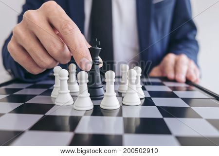 Close up of hands confident businessman playing chess game to development analysis new strategy plan leader and teamwork concept for success.