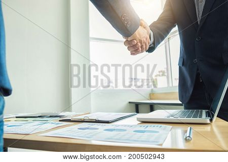 Two business men shaking hands during a meeting to sign agreement and become a business partner enterprises companies confident success dealing contract between their firms