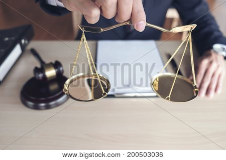 Close up of hand Male lawyer working with scales of justice gavel and note paper report the case on wooden table in office Law and justice concept.