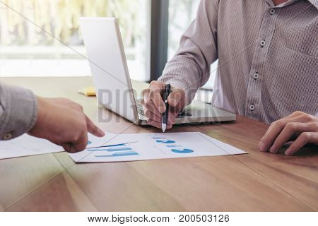 Business team two colleagues discussing new plan financial graph data on office table with laptop and calculator.