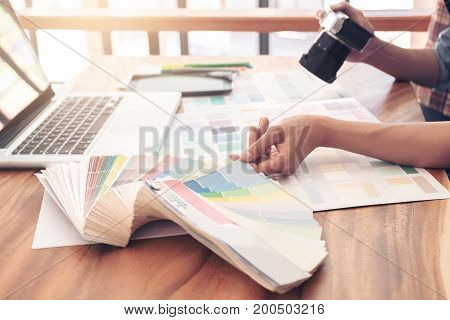 Color samples colour chart   sample Graphic designer being selecting Color band and graphics tablet at workplace with work example in camera and laptop on wooden desk.