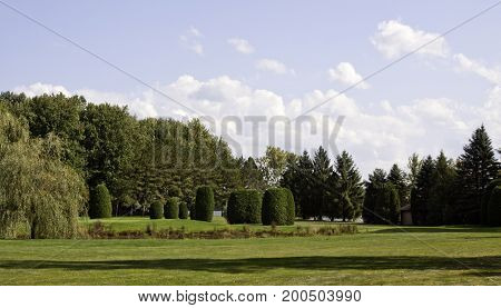 Wide view of a beautiful groomed landscape with trimmed lawn and trees with lots of greenery near Mont Joli, Quebec on a sunny day with big clouds in September.