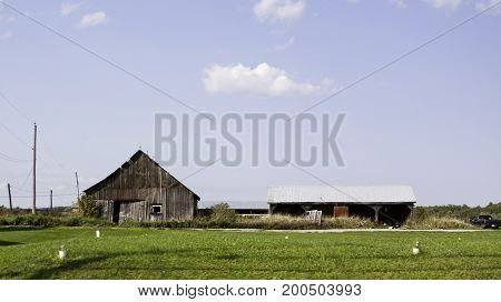 Wide view of an old abandoned barn alongside a covered structure with surrounding greenery. Shot from a country road in Maine, USA on a sunny day with clouds in September.