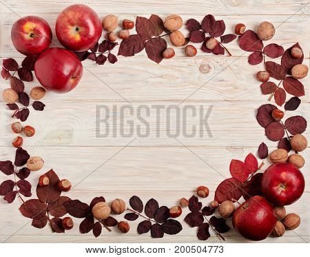 Flat lay frame of autumn crimson leaves hazelnuts walnuts and apples on a light wooden background. Selective focus.