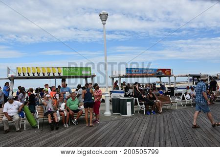 OCEAN CITY, MARYLAND - JUL 1: The famous Boardwalk in Ocean City, Maryland, seen on July 1, 2017. The city It features miles of beach and a wooden boardwalk lined with restaurants, shops and hotels.
