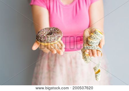 Close-up of woman's hands holding a donut and a measuring tape. The concept of healthy eating. Diet