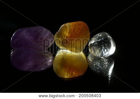 Several pieces of tumbled gemstones on a black mirror.