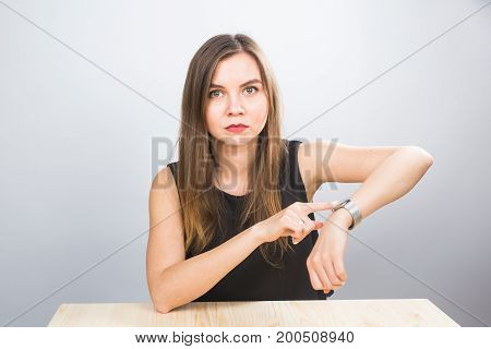 Time is over. Attractive brunette woman pointing to her hand reminding about time.