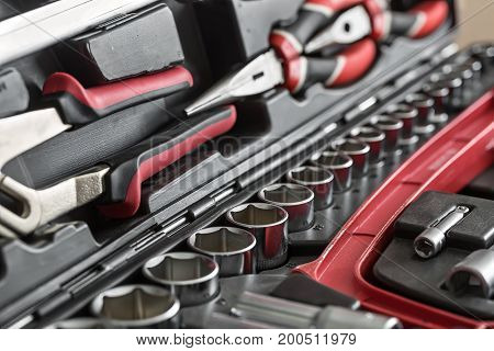Black-red pliers and a red saw in the dark toolbox. Between them there are different nozzles. Closeup low aperture photo. Horizontal.