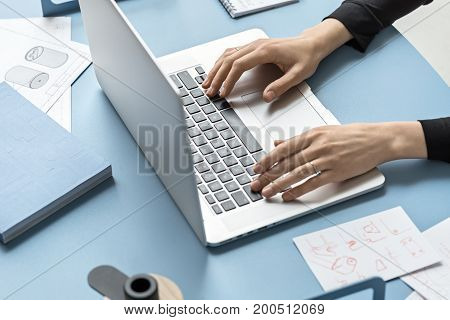 Girl is using a laptop on the metal blue table in the workshop. Around the laptop there are draughts, drafts, notebooks, marker and a pencil. Low aperture closeup photo. Horizontal.