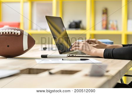 Female is using a laptop on wooden table on the blurry background of the yellow shelves in the office. Next to her there are football, markers and pencils, papers, book. Close up. Horizontal.