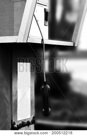 Ear Phone Of Public Pay Phone Hanging Down In White Tone (abandoned, Lonely Concept)