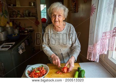 An elderly woman prepares a meal in a village house.