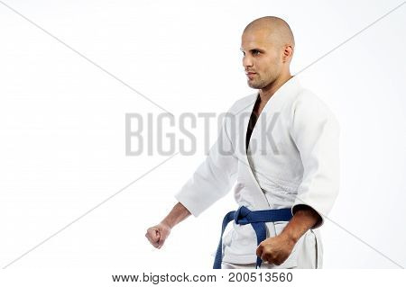 Young sporty bald man in white kimono for sambo jiu jits judo and other martial arts stands in battle rack on white isolated background side view