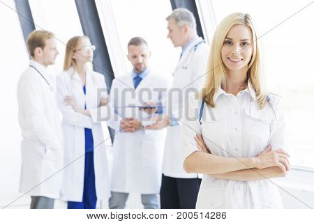 Successful female doctor and her team on background in clinical office